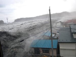防潮堤を乗り越えて町に押し寄せる津波