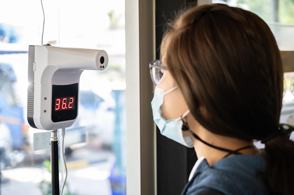 買い物街に入る前に、自動赤外線温度計で温度を測ろうとする女性。 COVID-19の世界的流行の人を識別するために使用する赤外線温度計。